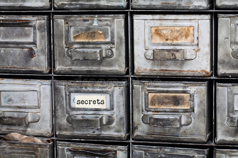 Secrets concept image. Closed archive storage, filing cabinet interior. aged silver metallic boxes with index cards stock image