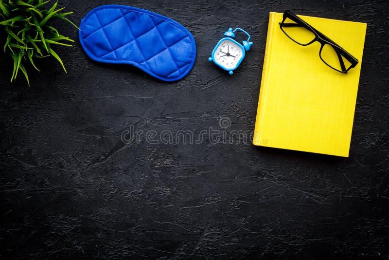 Secrets of good sleep. Right preparation for sleep. Reading before fell asleep. Sleeping mask near alarm clock and book. On black background top view stock photos