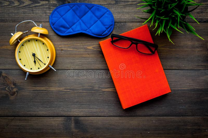 Secrets of good sleep. Right preparation for sleep. Reading before fell asleep. Sleeping mask near alarm clock and book. On dark wooden background top view royalty free stock photography