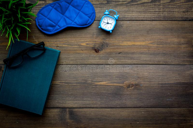 Secrets of good sleep. Right preparation for sleep. Reading before fell asleep. Sleeping mask near alarm clock and book. On dark wooden background top view royalty free stock photos