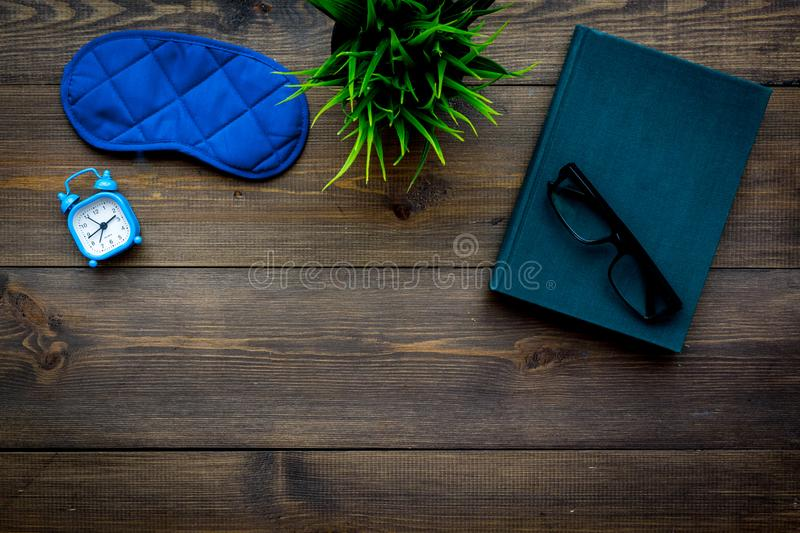Secrets of good sleep. Right preparation for sleep. Reading before fell asleep. Sleeping mask near alarm clock and book. On dark wooden background top view royalty free stock images