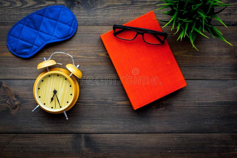 Secrets of good sleep. Right preparation for sleep. Reading before fell asleep. Sleeping mask near alarm clock and book. On dark wooden background top view stock photography