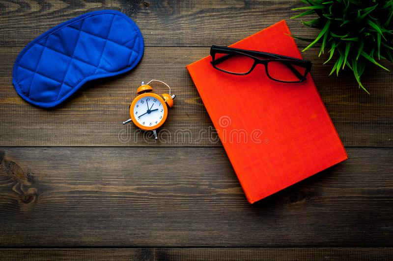 Secrets of good sleep. Right preparation for sleep. Reading before fell asleep. Sleeping mask near alarm clock and book. On dark wooden background top view stock images