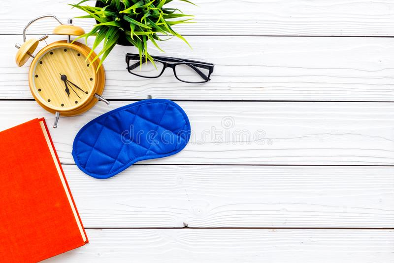 Secrets of good sleep. Right preparation for sleep. Reading before fell asleep. Sleeping mask near alarm clock and book. On white wooden background top view stock images