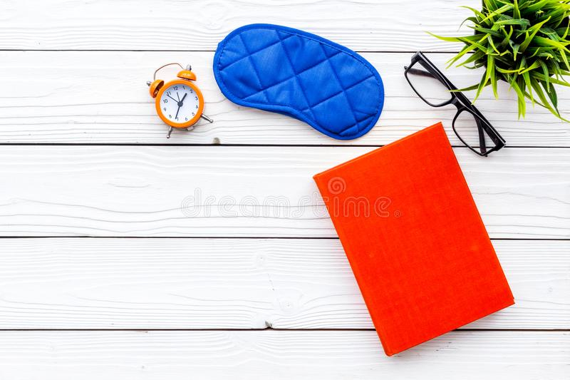Secrets of good sleep. Right preparation for sleep. Reading before fell asleep. Sleeping mask near alarm clock and book. On white wooden background top view royalty free stock images
