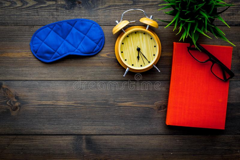 Secrets of good sleep. Right preparation for sleep. Reading before fell asleep. Sleeping mask near alarm clock and book. On dark wooden background top view royalty free stock image