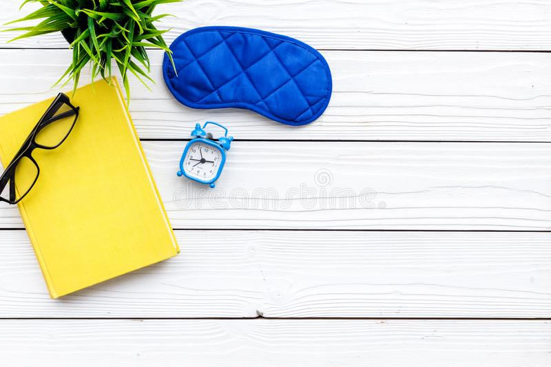 Secrets of good sleep. Right preparation for sleep. Reading before fell asleep. Sleeping mask near alarm clock and book. On white wooden background top view stock image