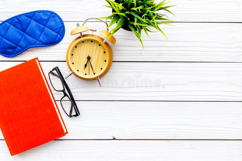 Secrets of good sleep. Right preparation for sleep. Reading before fell asleep. Sleeping mask near alarm clock and book. On white wooden background top view stock photos