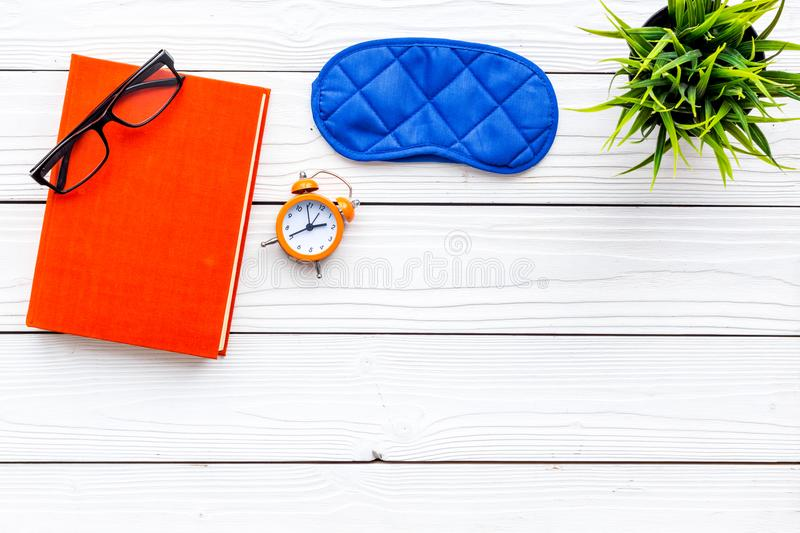 Secrets of good sleep. Right preparation for sleep. Reading before fell asleep. Sleeping mask near alarm clock and book. On white wooden background top view royalty free stock photography