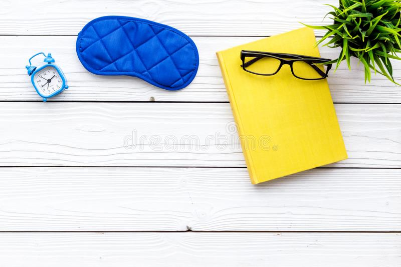 Secrets of good sleep. Right preparation for sleep. Reading before fell asleep. Sleeping mask near alarm clock and book. On white wooden background top view royalty free stock image