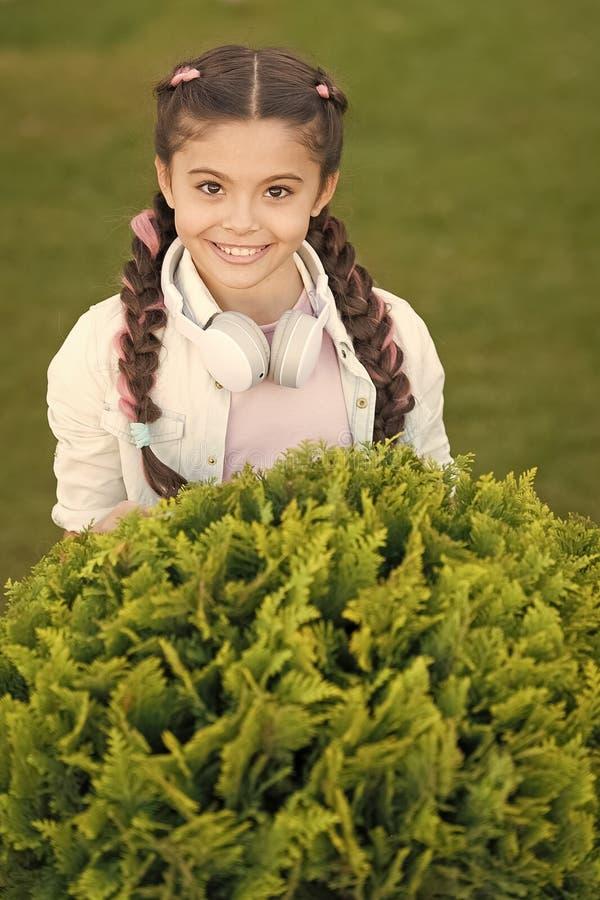 Secrets ? ?lever l'enfant heureux Fond mignon d'herbe verte d'enfant de fille Enfant heureux ?motif en bonne sant? d?tendant deho photo stock