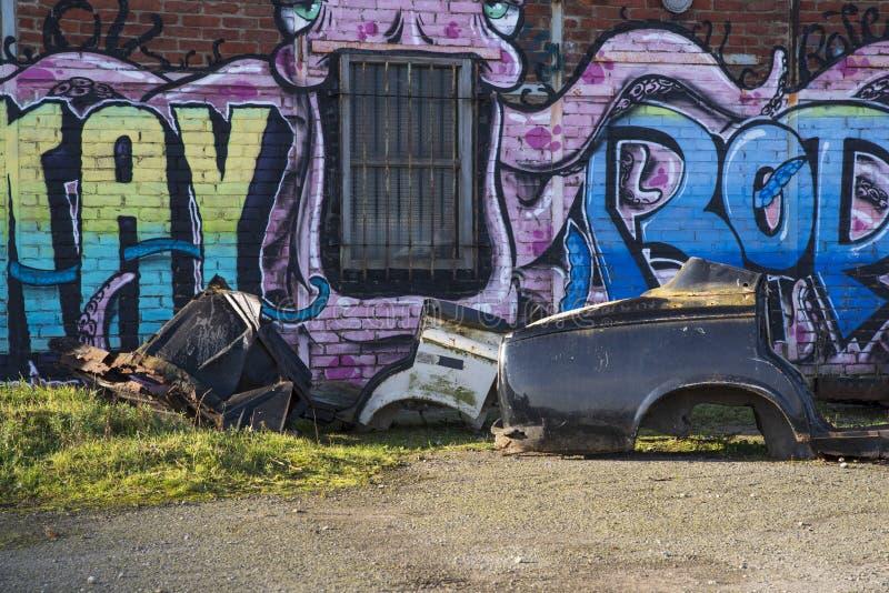 Secteur abandonné avec un petit morceau de graffiti et une épave de voiture images libres de droits