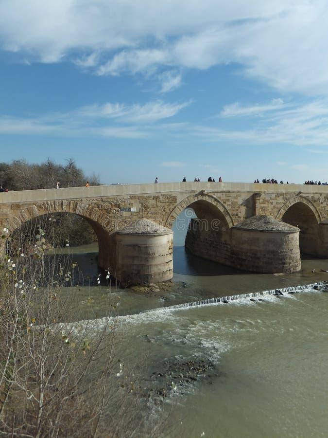 Sectie van Roman Bridge in Cordoba over de rivier van Guadalquivir op een heldere zonnige dag tegen blauwe hemel met kleine cijfe stock foto