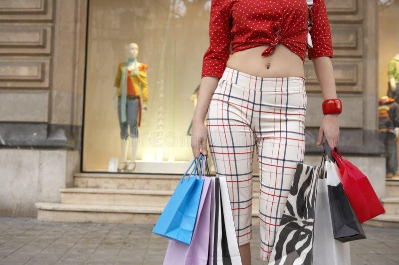 Sectiom de la mujer que se coloca con los bolsos de compras foto de archivo