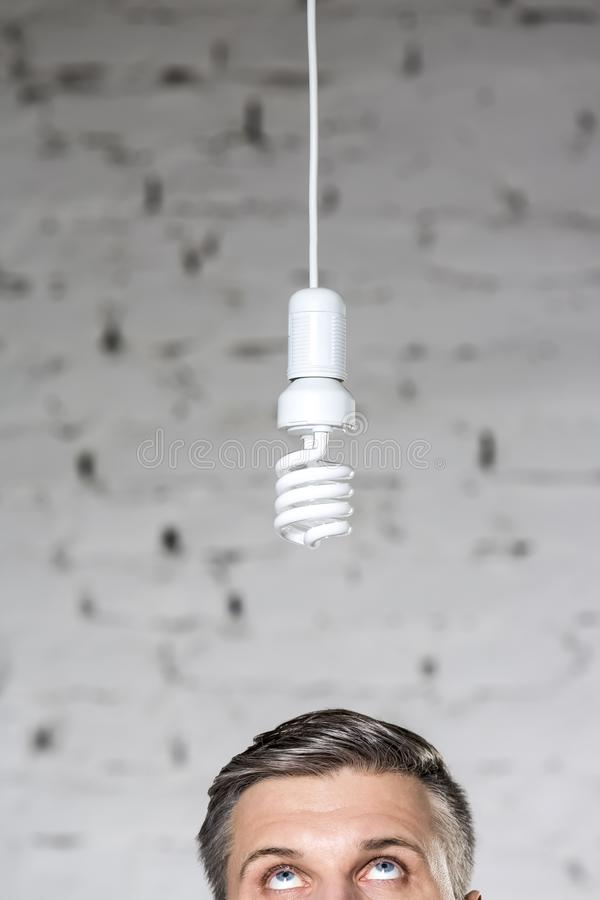 Section élevée de l'homme d'affaires mûr réfléchi regardant l'ampoule de rendement optimum accrochant contre le mur de briques au photo libre de droits