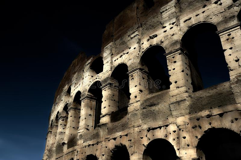 A section of the facade of the Colosseum Flavian Amphitheatre in Rome during the blue hour. Night view. Rome, Lazio, Italy.  stock images