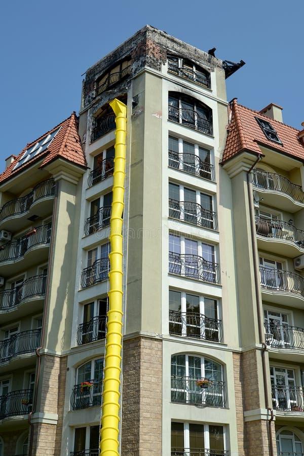 Section jaune de construction de descendeur d'ordures sur la réparation du bâtiment résidentiel après le feu image stock