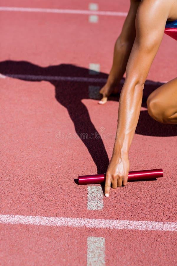 Section médiane d'athlète féminin prête à commencer la course de relais image stock
