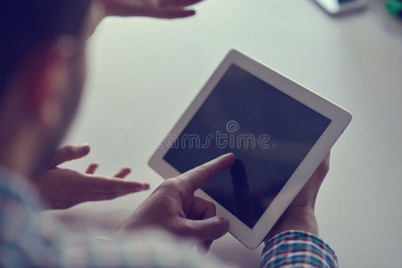 Section médiane d'homme d'affaires utilisant le comprimé numérique dans le bureau photo stock