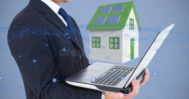 Section médiane d'homme d'affaires tenant l'ordinateur portable contre la maison 3d image stock