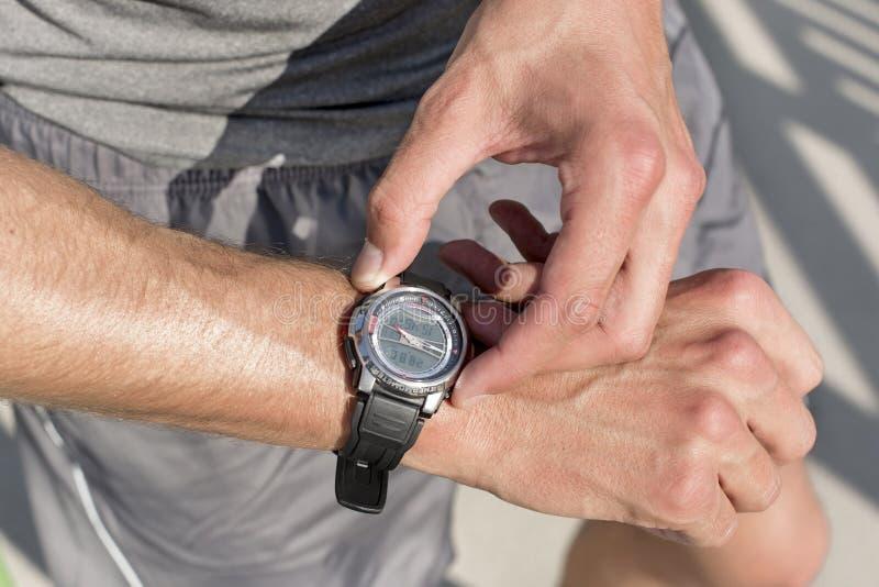 Section médiane d'homme d'ajustement vérifiant le temps sur le chemin en parc photos libres de droits