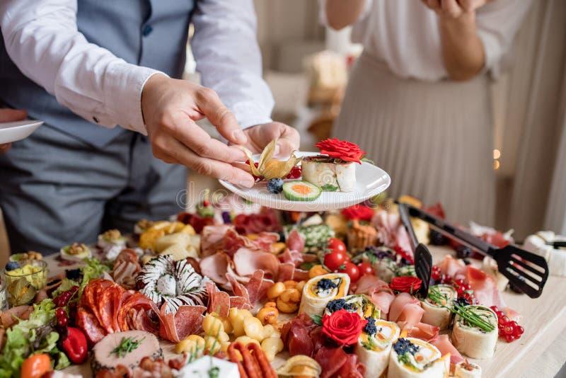 Section médiane d'un homme mettant la nourriture sur le plat sur une fête d'anniversaire d'intérieur de famille photos stock