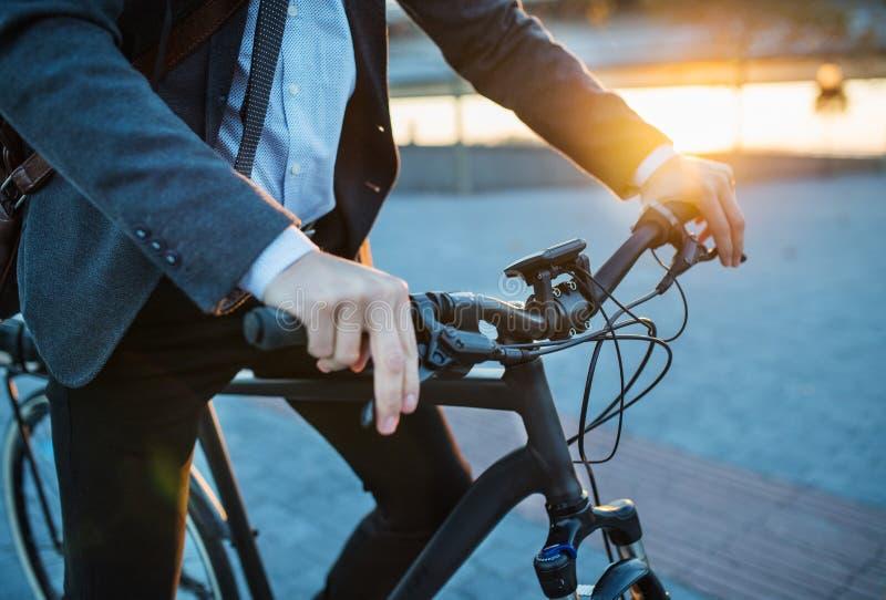 Section médiane de banlieusard d'homme d'affaires avec la bicyclette électrique voyageant du travail dans la ville photos stock
