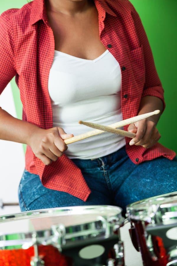 Section médiane de batteur féminin Holding Drumsticks photo stock