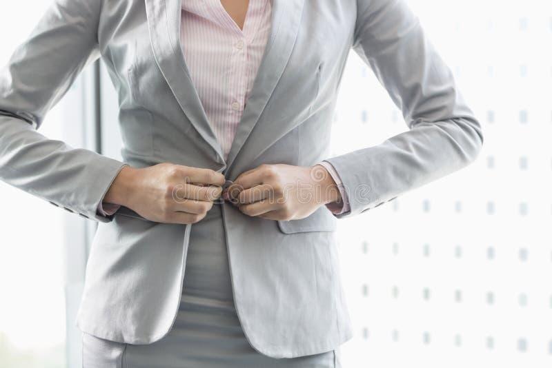 Section médiane de femme d'affaires boutonnant son blazer images stock