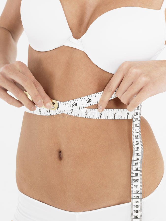 Section médiane de femme dans le soutien-gorge blanc mesurant sa taille photographie stock