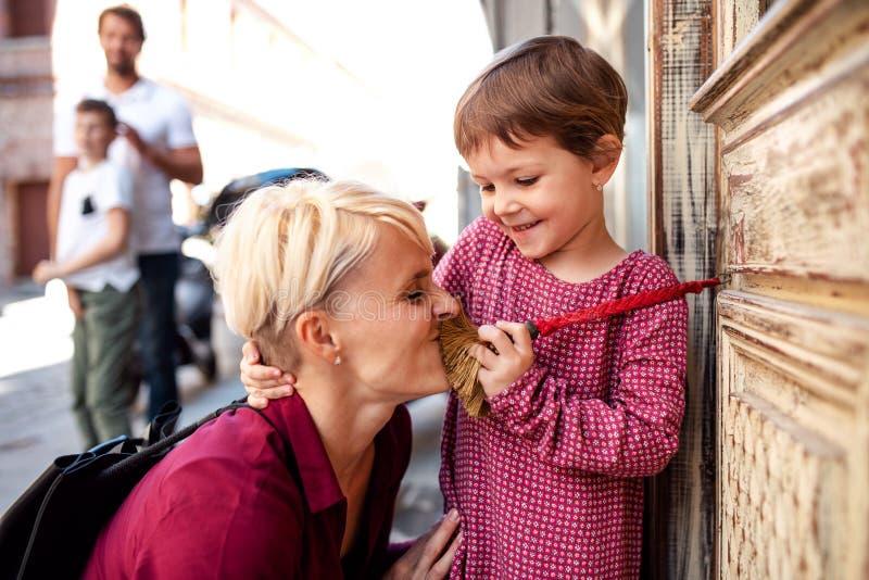 Section médiane de jeune famille avec deux petits enfants dehors en ville, ayant l'amusement photos stock