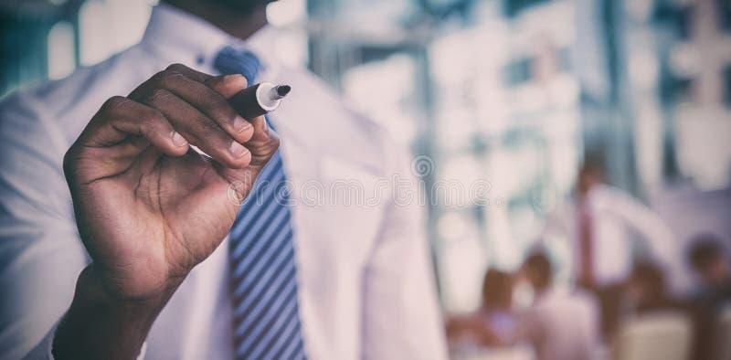 Section médiane de l'écriture d'homme d'affaires avec le marqueur sur le verre photo stock