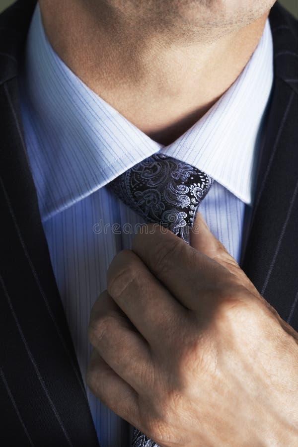 Section médiane de l'homme dans le costume ajustant la cravate photos stock