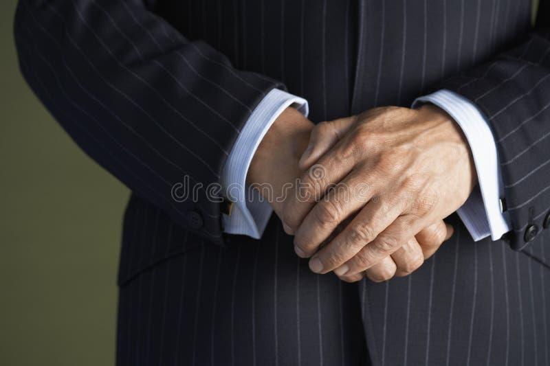 Section médiane de l'homme dans le costume avec des mains étreintes photographie stock
