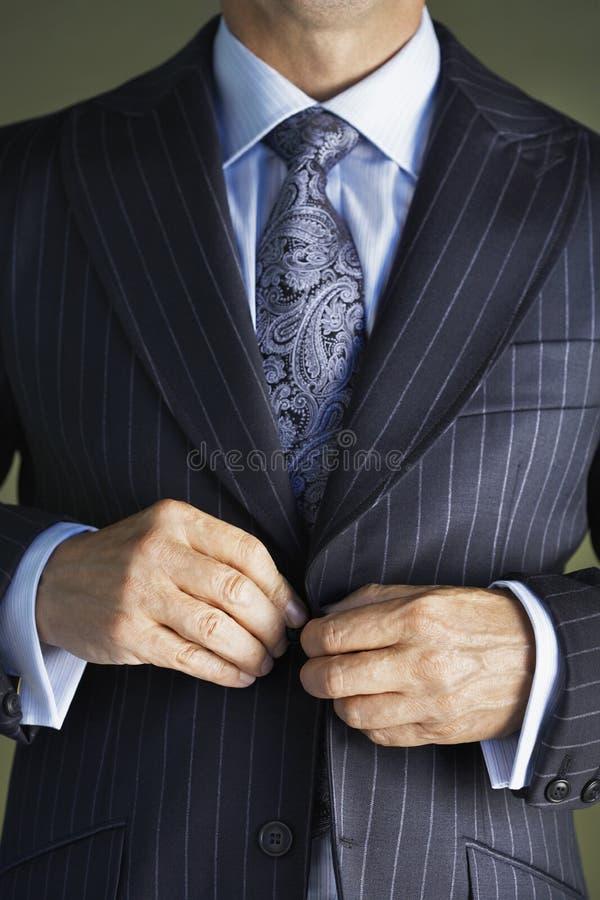 Section médiane de l'homme dans le costume boutonnant le bouton sur le manteau image stock