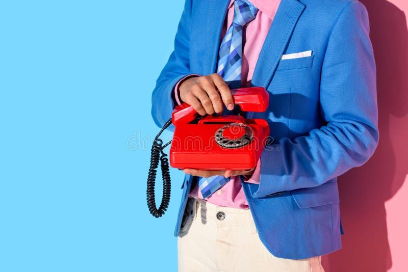 Section médiane de l'homme dans le costume formel avec le rétro téléphone dans des mains sur le rose photos libres de droits