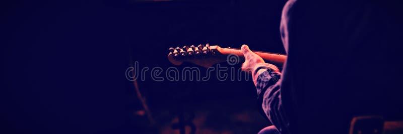 Section médiane de l'homme jouant la guitare photo libre de droits