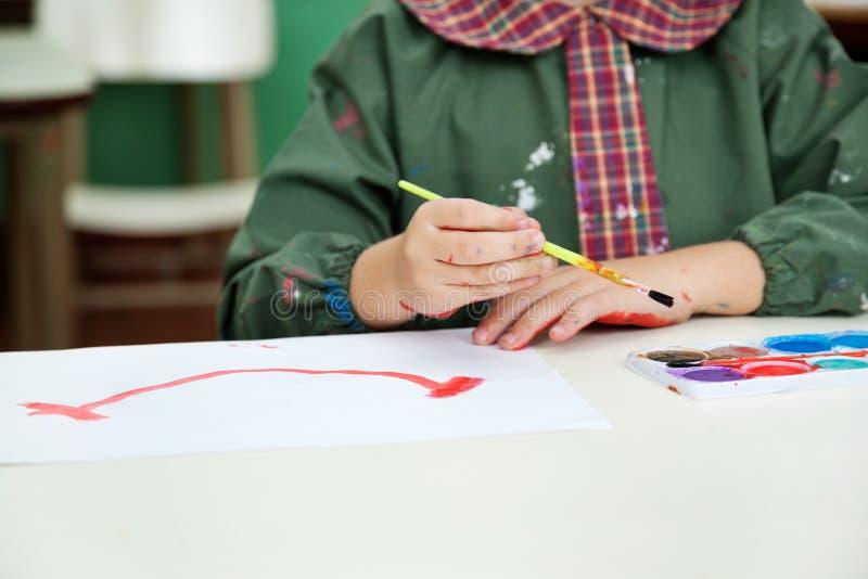 Section médiane de la peinture de garçon au bureau photo stock