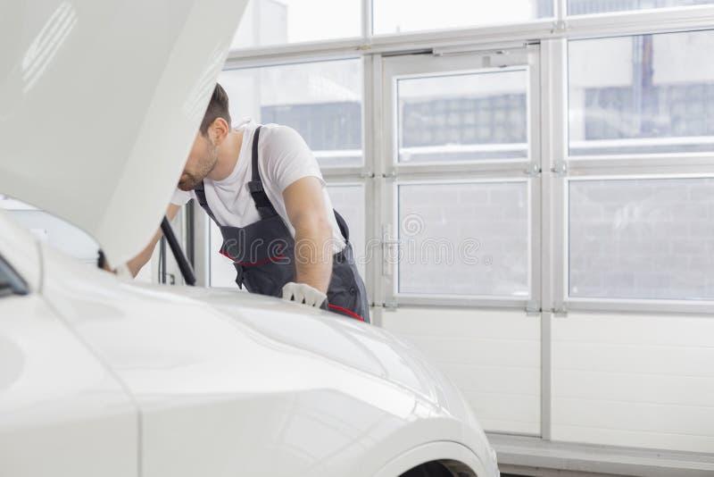 Section médiane du technicien masculin réparant le moteur de voiture dans l'atelier image libre de droits
