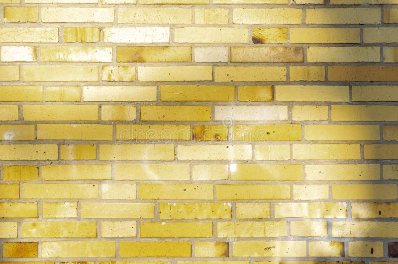 Section of an old partially weathered and polluted building wall of yellow to brownish clinker bricks with soft shadows of trees. And other things stock photography