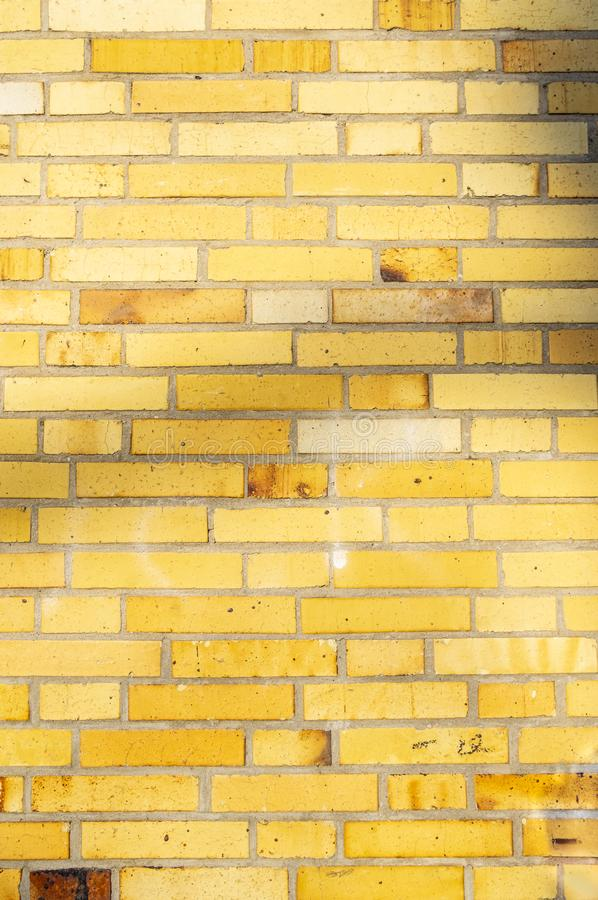 Section of an old partially weathered and polluted building wall of yellow to brownish clinker bricks with soft shadows of trees. And other things royalty free stock image