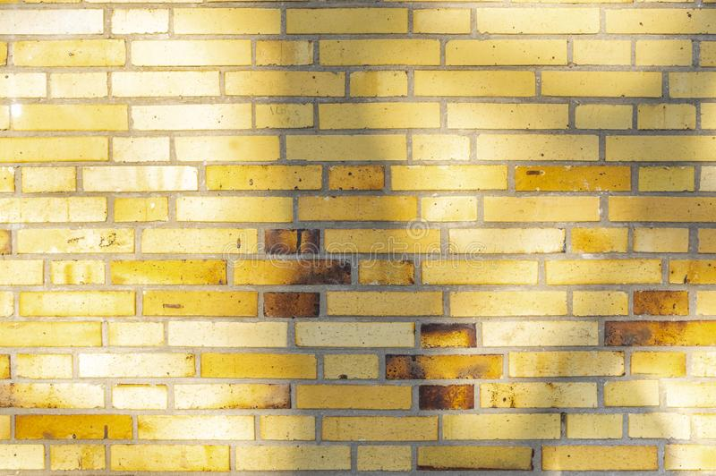 Section of an old partially weathered and polluted building wall of yellow to brownish clinker bricks with soft shadows of trees. And other things royalty free stock photo