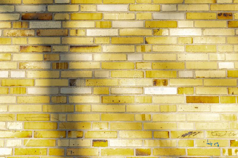 Section of an old partially weathered and polluted building wall of yellow to brownish clinker bricks with soft shadows of trees. And other things royalty free stock images