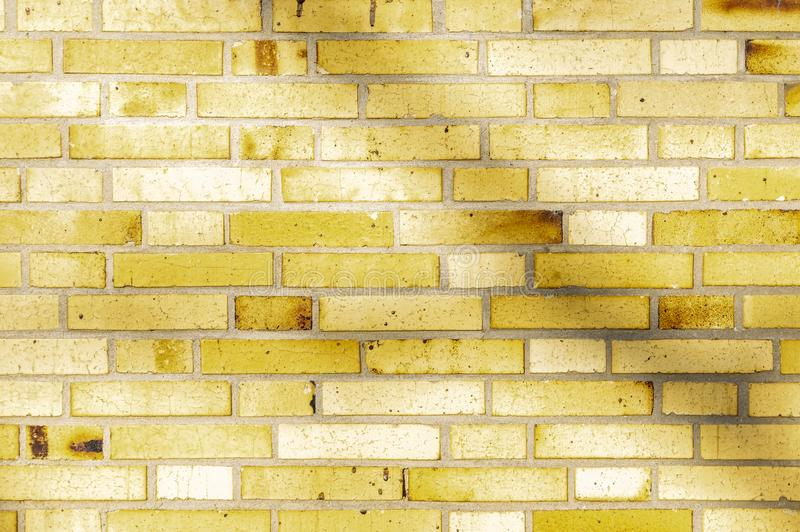 Section of an old partially weathered and polluted building wall of yellow to brownish clinker bricks with soft shadows of trees. And other things stock photo