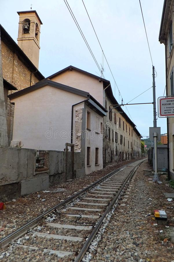 Section of a single-track railway in Como, Italy, running in a narrow space between houses, with a church belfry visible above stock image