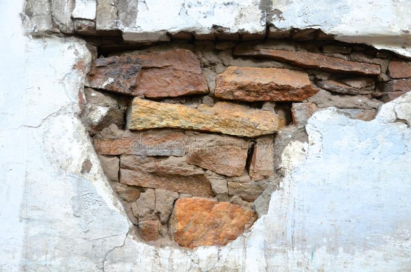 A section of stone wall with plaster removed. The section of the stone wall with the outer plaster removed stock images