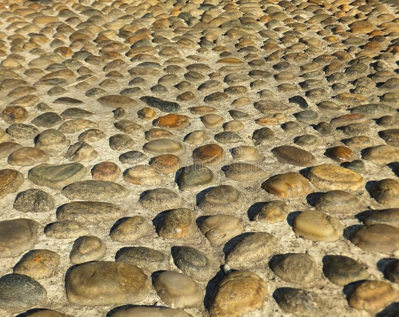 Section of a street in Milan paved with natural golden-coloured cobbles, casting their own little shadows stock photography