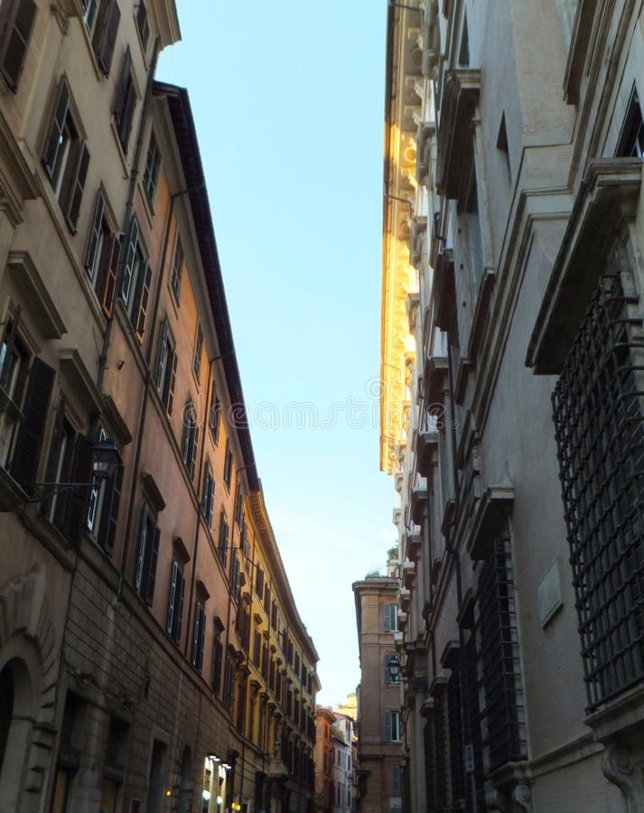 Section of a street in Rome, Italy, with a stripe of blue sky enclosed between two partly sunlit houses royalty free stock photo