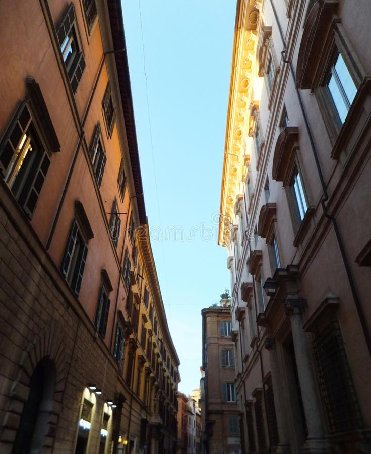 Section of a street in Rome, Italy, with a stripe of blue sky enclosed between two partly sunlit houses royalty free stock images