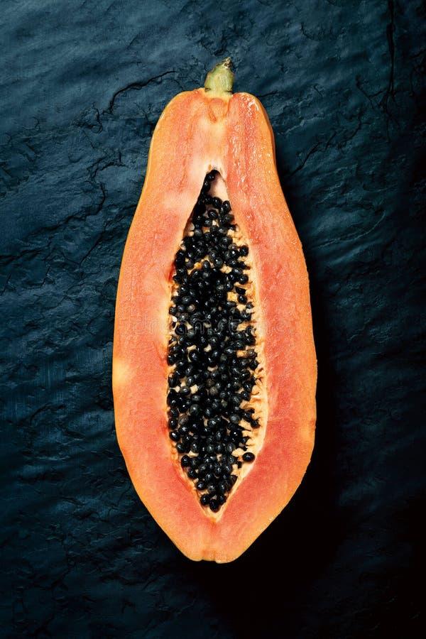 Section transversale de papaye sur l'ardoise foncée photographie stock libre de droits